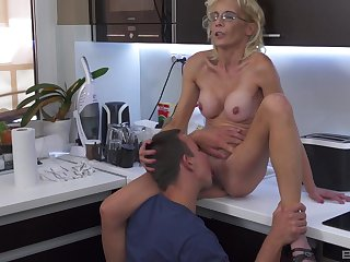 Skinny mature blonde mixes pile it on with a young fella in a difficulty kitchen
